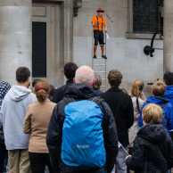 Street performer juggling knives on stilts