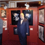 Cemal in front of the mini exhibit, two more photographs on the other side