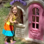Mina in front of her play house